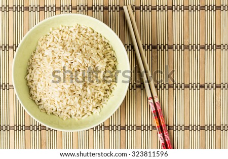 Boiled brown rice on bamboo washer with chopsticks - stock photo