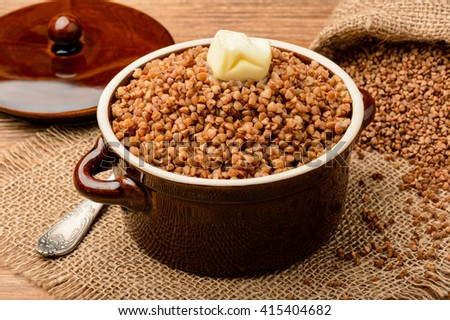 Boiled buckwheat porridge in ceramic pot on wooden background.