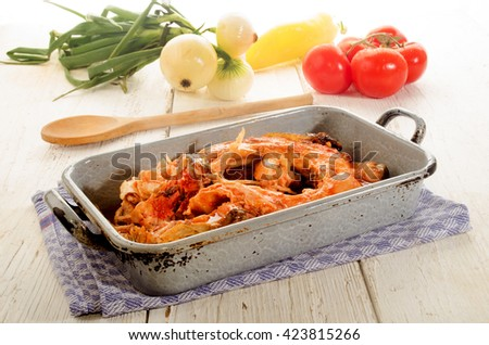 boiled carp in a rustic gray metal cooking tin, white onion and tomato - stock photo