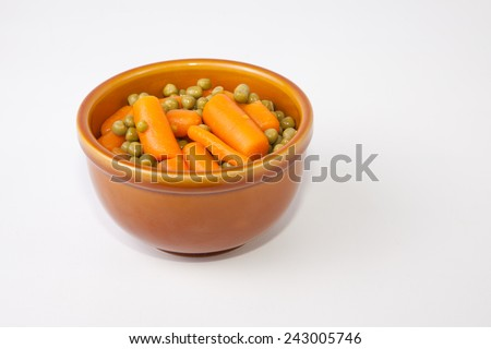 Boiled carrots and green peas on rustic glazed clay bowl. Isolated over white background - stock photo