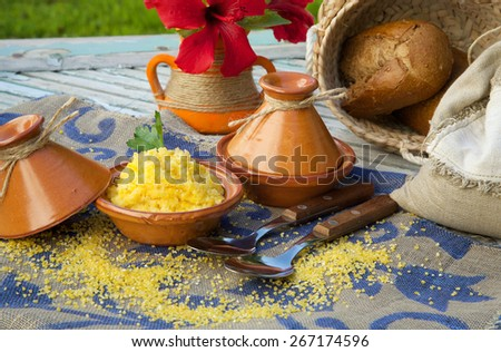 Boiled corn cereal in tajine. Raw corn cereal,whole grain bread,hibiscus flower in the background - stock photo