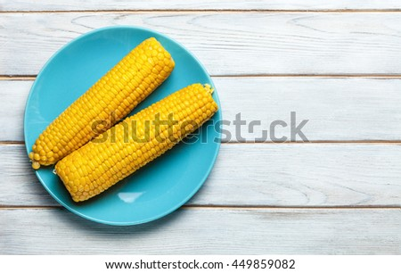 boiled corn on blue plate on white wooden background - stock photo