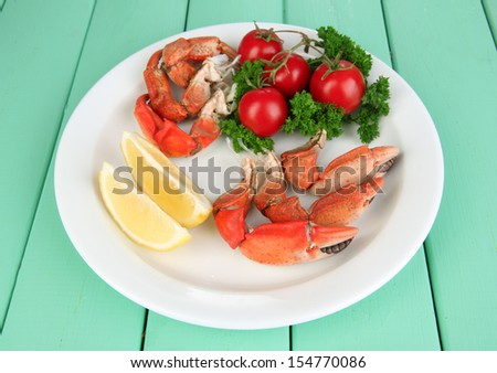 Boiled crab claws on white plate with salad leaves and tomatoes,on wooden table background