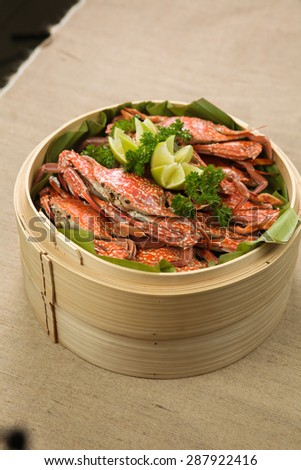 boiled crab with lemon on a bamboo steam pot - stock photo