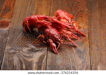 boiled crayfish on wooden surface - stock photo