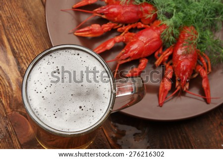 boiled crayfish on wooden surface with a beer and dill.old style plate - stock photo