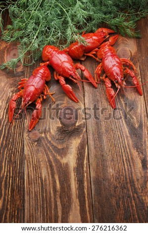 boiled crayfish on wooden surface with dill - stock photo