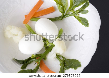 boiled egg and veggie on white plate - stock photo