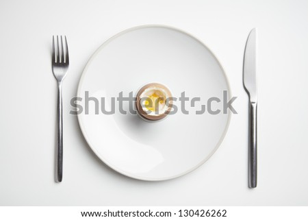 Boiled egg on plate with knife and fork on white table top - stock photo