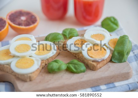 Boiled egg toasts and glass of blood orange juice