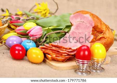 Boiled ham, painted Easter eggs and tulips on rustic table - stock photo