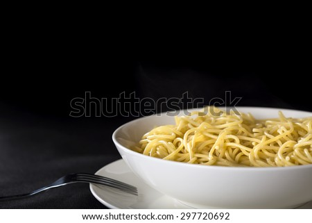 Boiled Italian spaghetti in plate over black background with copy space - stock photo