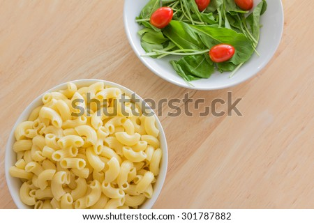 Boiled macaroni pasta and rocket salad with cherry tomatoes both in a white dishes on a wooden table - stock photo
