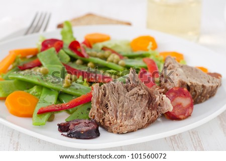 boiled meat with sausages and vegetable salad