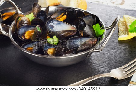 Boiled mussels in cooking dish on a dark background. Selective focus - stock photo