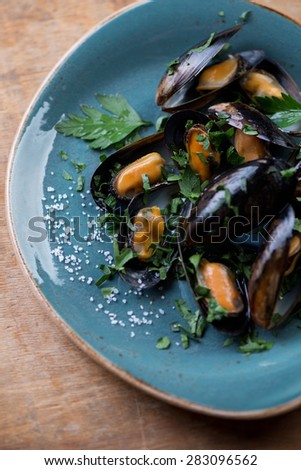 Boiled mussels served with fresh parsley and sea salt, close-up, selective focus - stock photo