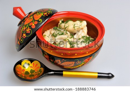 Boiled pelmeni in khokhloma painted russian wooden dishes with spoon on gray - stock photo