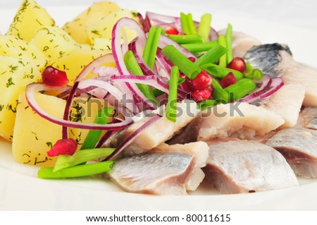 Boiled potato with a herring and an onions