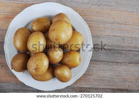 boiled potatoes in their skins on a plate - stock photo