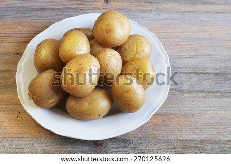 boiled potatoes in their skins on a plate, wooden background - stock photo