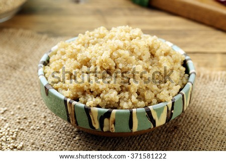 boiled quinoa in ceramic bowl rustic background - stock photo