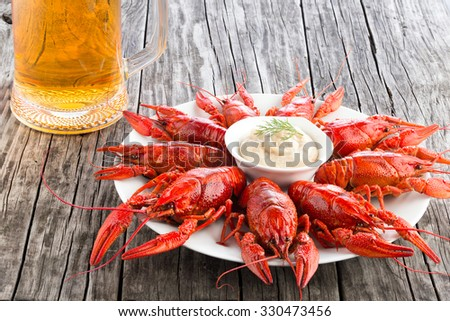 Boiled red crayfishes on a white dish with sauce of grated horseradish in a gravy boat with glass of fresh lager beer - stock photo