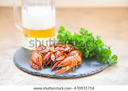 Boiled red crayfishes with a beer and green vegetableson a ceramic board. Close up. Selective focus.