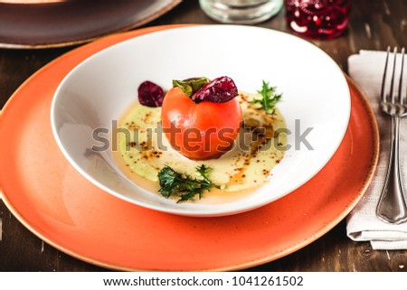 Boiled red tomato without skin on sauce in bowl. Decorated with leaves, beautiful serve. Closeup. Lenten menu, diet food. Glass in background, wooden table, fork
