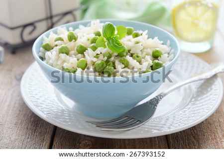 Boiled rice with green peas - stock photo
