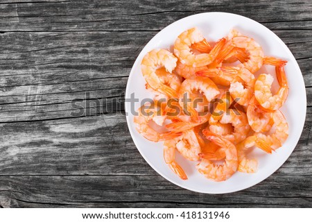 boiled tails of king shrimps on a white dish on an old rustic table, blank space left, top view, studio lights - stock photo