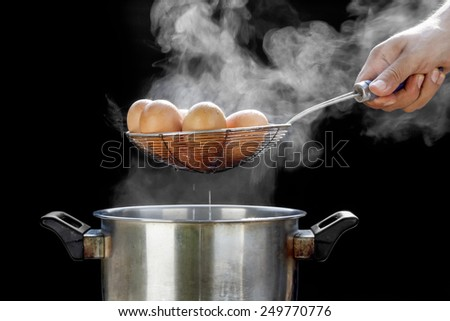 boiling eggs in stainless steel pot - stock photo