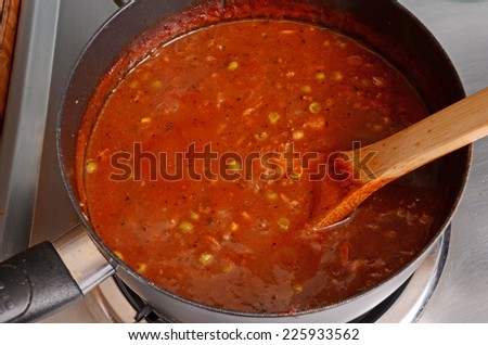 Boiling hot homemade vegetable soup in medium sauce pan on electric stove with wooden stir spoon. - stock photo