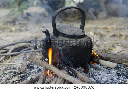 Boiling hot water with kettle on bonfire - stock photo