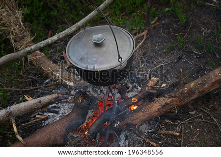 Boiling pot at the campfire - stock photo