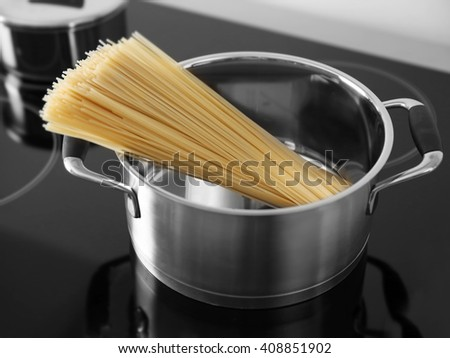 Boiling spaghetti in pan on electric stove in the kitchen - stock photo
