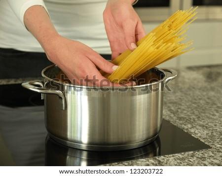 Boiling spaghetti pasta for delicious Italian dish - stock photo