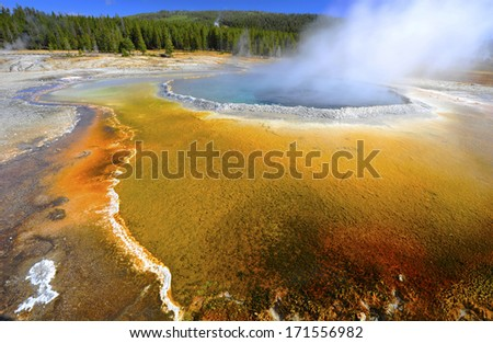 boiling steamy water in colorful thermal pool/ geyser, yellowstone national park, wyoming, united states - stock photo