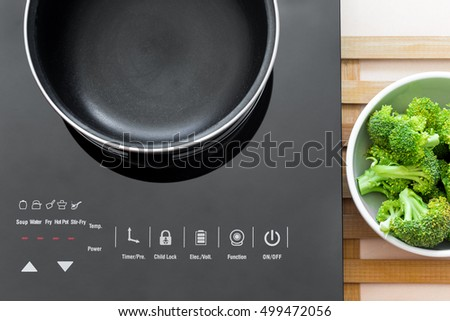 Boiling water at pan on Induction stove top panel for cooking broccoli, closeup