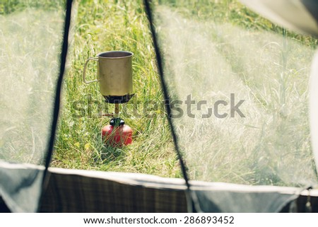 boiling water in titanium mug on portable camping stove - stock photo