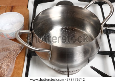 Boiling water into saucepan. Cooking buckwheat groats on gas stove. - stock photo