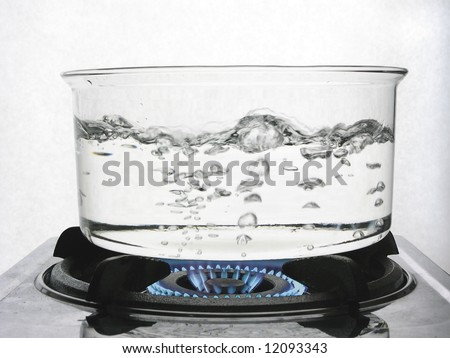 Boiling water on gas flame - stock photo