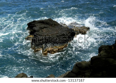 Boiling waters around rock offshores on Kauai, Hawaii.  Turbulent waters wash rugged outcrop. - stock photo