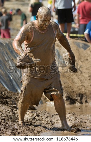 BOISE, IDAHO - AUGUST 25: Unidentified runner walks without his shoes at the Dirty Dash August 25 2012 in Boise, Idaho - stock photo