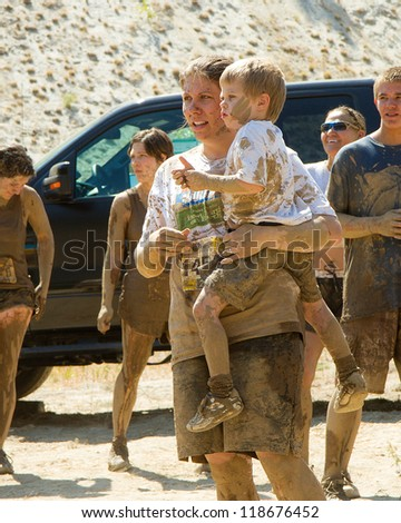 BOISE, IDAHO - AUGUST 25: Unidentified woman holding her child covered in mud at the Dirty Dash August 25 2012 in Boise, Idaho - stock photo