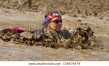 BOISE, IDAHO - AUGUST 25: Unidentified woman swims in the muck and mud at the Dirty Dash August 25 2012 in Boise, Idaho - stock photo