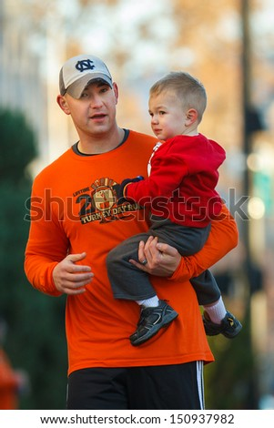 BOISE, IDAHO - NOVEMBER 22:  Man holds his son while competing in The 5k Turkey Day race in Boise, Idaho on November 22, 2012 - stock photo