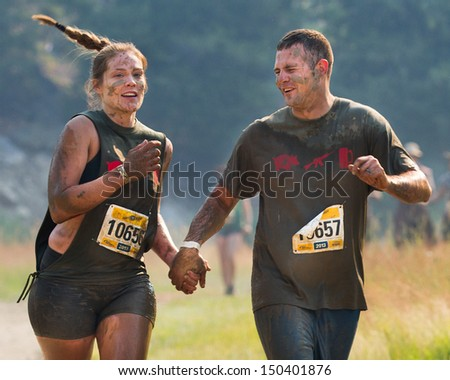 BOISE, IDAHO/USA - AUGUST 10: Couple 10656 and 10657 hold hands while running at the The Dirty Dash in Boise, Idaho on August 10, 2013  - stock photo