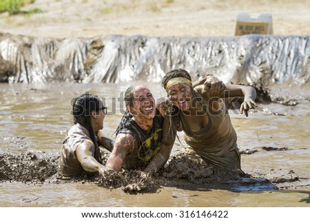 BOISE, IDAHO/USA - AUGUST 11, 2013: Group of women falling into the mud during the Dirty Dash in Boise, Idaho - stock photo