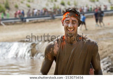 BOISE, IDAHO/USA - AUGUST 11: Man covered in mud smiles at the camera during the The Dirty Dash in Boise, Idaho on August 11, 2013  - stock photo