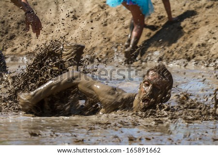 BOISE, IDAHO/USA - AUGUST 10: Person swims through the mud pond on his way to the finish line at the The Dirty Dash in Boise, Idaho on August 10, 2013 - stock photo
